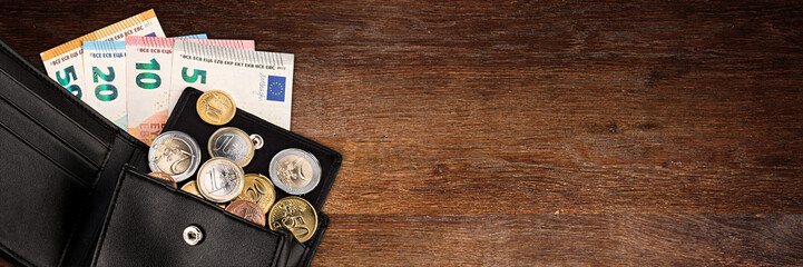euro coin and bank note in black leather wallet on wide wood wooden panorama business finance background with copy space