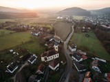 aerial view of houses, church and green fields at foggy sunrise, Germany