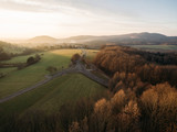 aerial view of beautiful hills with vegetation, trees and road at sunrise, Germany