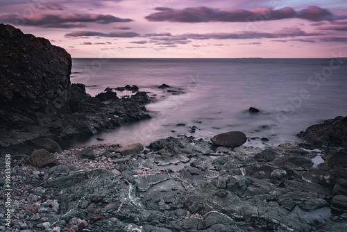 Fotobehang Lavendel Sunset at rocky beach