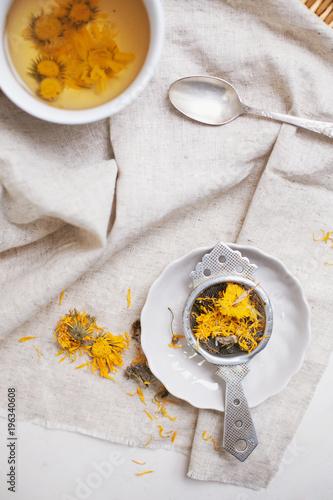 Herbal calendula tea in white cup and strainer