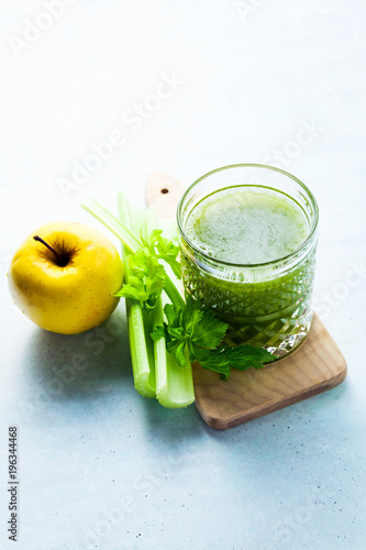 Foto op Canvas Sap freshly squeezed celery and apple juice in a glass on a wooden small board on the table. concept and recipe for a healthy diet