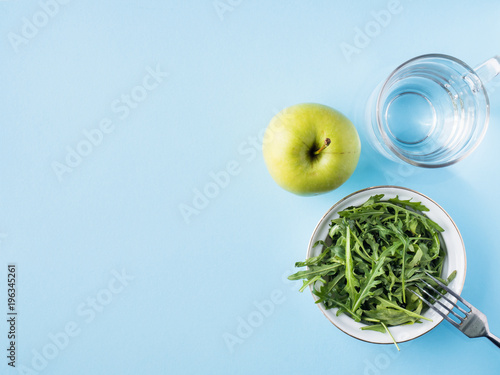 Diet leaves salad green Apple a glass of water on blue background