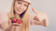 Girl showing fresh strawberries - 196355261