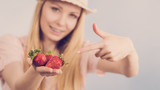 Girl showing fresh strawberries - 196355261