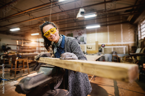 Professional carpenter woman choosing and preparing wood at steel vise in the fabric workshop. - 196358479