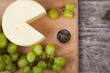 Cheese and grapes on a cutting board - 196363410