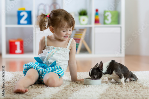 Three years old child toddler sitting on carpet and feeding his little dog