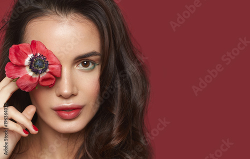 Papiers peints Spa Beautiful brunette girl with green eyes make up and fresh skin posing at red background with flower, skin care concept, beauty spa, bio product. Horizontal