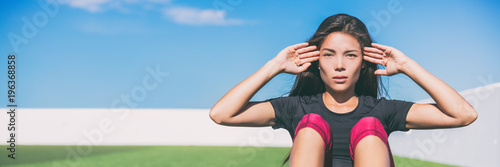 Wall mural Sit ups - fitness woman exercising sit up outside in grass in summer. Fit athlete crossfit training in summer. Asian sports model in her 20s banner panorama with copy space.