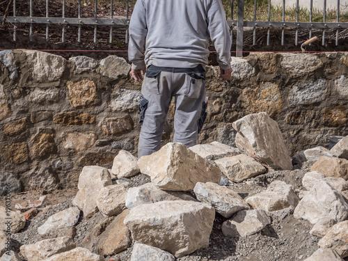 Tuinposter Baksteen muur Mann beim Natursteinmauer