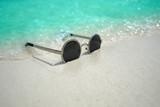 Sunglasses on sandy beach in summer.