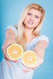 Woman holds grapefruit citrus fruit in hands