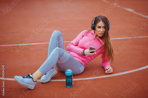 Fotobehang Jogging Young woman resting and listening music after jogging