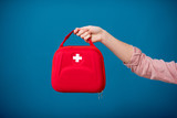 Holding first aid kit on the blue background - 196395869