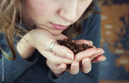 Foto Spatwand Koffiebonen Granos de café tostado de importación en la mano de una mujer