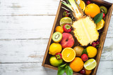 Fruit and berries in wooden tray top view..