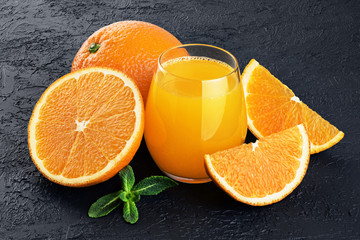 Glass with orange juice, oranges and mint on a dark background.