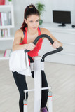 sporty woman training on step machine in bright living room - 196407433