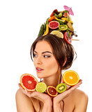 Hair mask from fresh fruits on woman head with vitamins for scalp. Girl with beautiful face and hairstyle hold halves of orange for skin and body therapy. Improvement of skin condition.