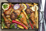 Grilled spicy chicken legs with pepper, lemon and potatoes