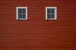Two windows (that look like eyes) on the side of a red barn in rural Iowa (Midwest, USA)