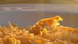 Grated cheese falls on the top of steaming scrambled eggs. - 196449000