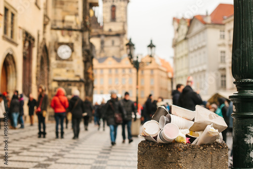 Prague A crowded trash can on Prague's main square during the Christmas break. Many people are blurry in the background. Pollution of city streets with trash on holidays.