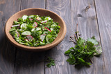 Vitamin salad of wild herbs with cucumber, radish and green onions in a wooden bowl on a wooden background. Healthy detox diet food - 196454064