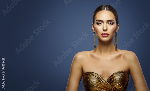Fashion Model Beauty Studio Portrait, Beautiful Woman Face Makeup, attractive Girl in Golden Dress looking at camera, on Blue Background
