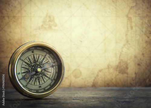 Fototapeta Old vintage retro compass on ancient map background. Travel geography navigation concept background.