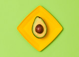 Avocado Tropical Fresh Fruit. Vegan Organic Food Concept. Flat lay. Trendy fashion Style. Minimal Design Art. Hot Summer Vibes. Green avocado on yellow plate. Bright Color. - 196460476