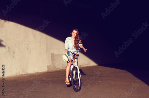 Poster Young woman sitting on city bicycle. Outdoor lifestyle portrait of girl with cruiser.
