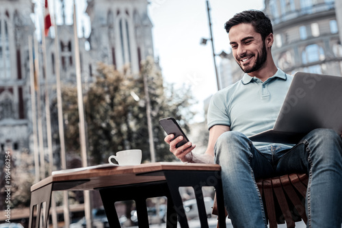 Good news is the best news. Low angle shot of a bearded guy grinning broadly while sitting outdoors with a laptop and using his smartphone.