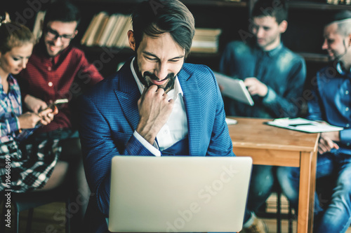 sales Manager with laptop on the background of business team in