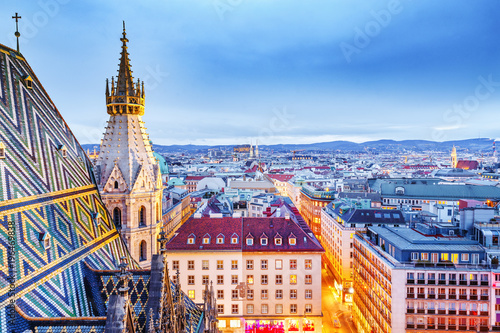 Leinwanddruck Bild Vienna, Austria, Europe. Lovely twilight skyline view from above of Vienna. Iconic landmark and extremely popular European travel destination. View over roofs on classic architecture, dusk scenery.