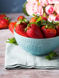 Fototapety Fresh spring strawberries in blue bowl with heart and pink roses in the background