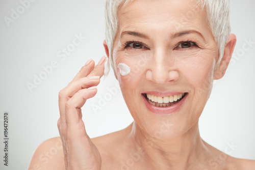canvas print picture Head shot of beautiful senior woman putting on the cream.