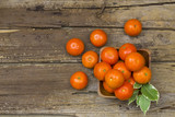 fresh tangerines in a bowl on wooden background