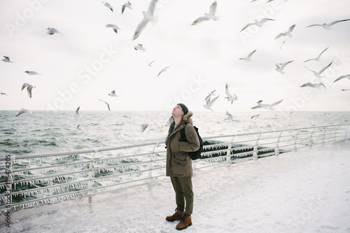 young man standing on quay and looking on seagulls