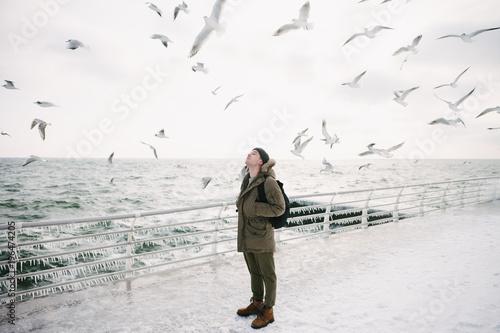 młody człowiek stojący na nabrzeżu i patrząc na mewy