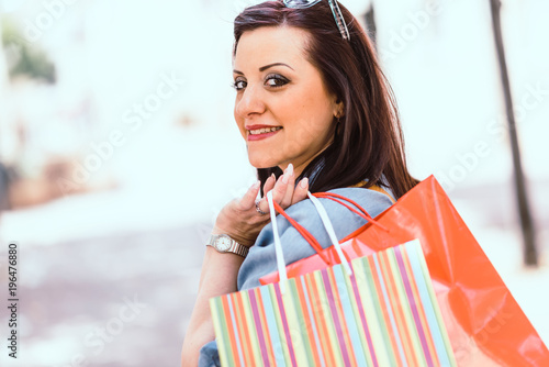 Poster Young woman walking with shopping bags in hand