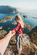 Couple follow holding hands traveling lifestyle on cliff mountain summer vacations outdoor in Norway