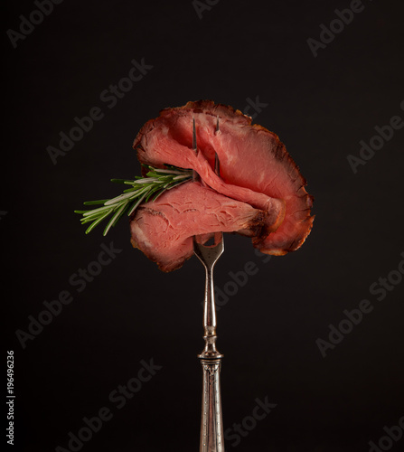Sliced medium rare grilled roast beef ribeye steak on dark slate kitchen plate background - 196496236