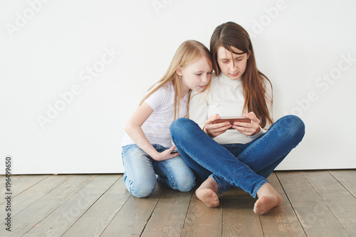 Two teenage girls on a white background playing games on the phone. Gambling addiction