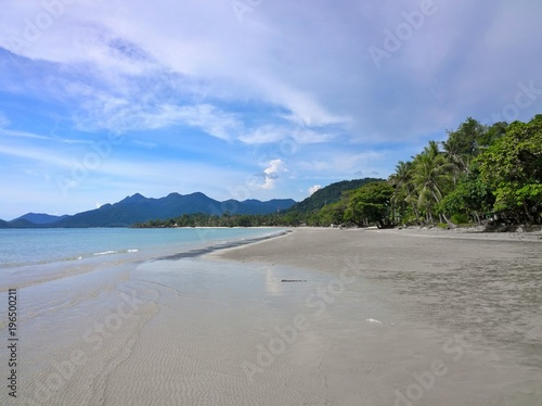 Fotobehang Tropical strand Blue sky and clouds over a tropical beach with green palm trees on Koh Chang island in Thailand