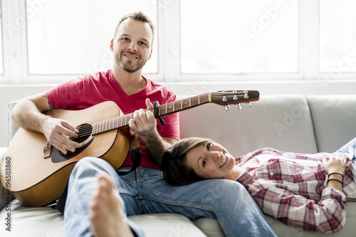 Young couple sitting on sofa in living room and playing guitar