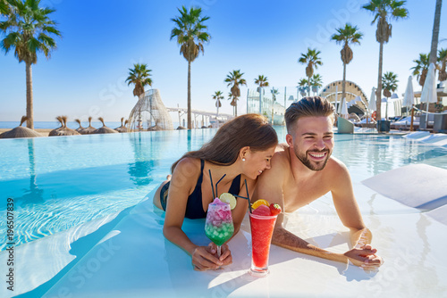 Young couple on infinity pool cocktails