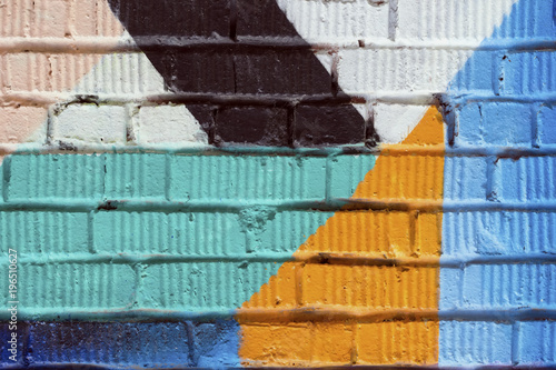 Abstract detail of brick wall with fragment of colorful graffiti. Urban Art close-up, for background use. - 196510627