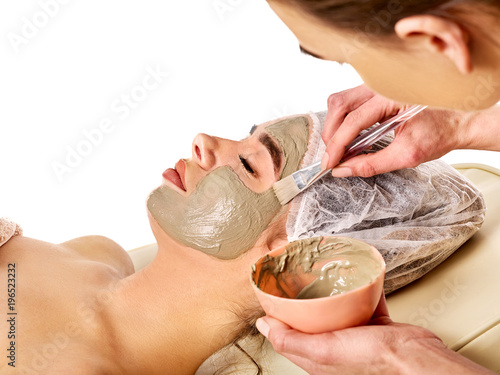 Fotobehang Spa Mud facial mask of woman in spa salon. Massage with clay full face. Girl on with therapy room. Beautician with brush therapeutic procedure isolated background. Healing clay for face. Acne Removal.